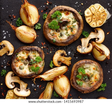 Stuffed portobello mushrooms stuffed with mozzarella and gorgonzola cheese and aromatic herbs on a black background, top view. Vegetarian food Stock photo ©