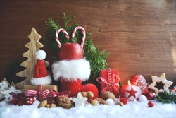 Stuffed red Santa Claus boot with apple and candy cane.Christmas background