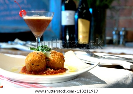 Stuffed Risotto balls, fried golden brown with a spicy tomato sauce and cocktail.
