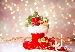 Stuffed Santa Claus boot with sweets, gift box and gingerbread man in the snow.Cute background with bokeh golden lights