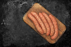 Stuffed Sausages on Old Wooden Cutting Board and Black Table Background, Top View. Raw Sausages In Natural Casing. Cookout Food. Uncooked Sausages For Grilling or Frying on Wood Board, Overhead View.