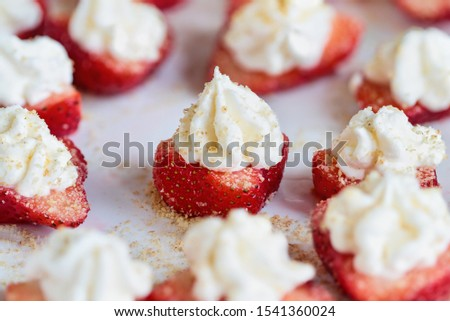 Stuffed strawberries filled with cheesecake filling made with whipped cream and cream cheese. Sprinkled with graham cracker crumbs. Selective focus with blurred foreground and background. #1541360024