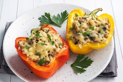 Stuffed sweet peppers with rice mushrooms and cheese with herbs. Baked halves of red and yellow peppers with filling. White wooden background.
