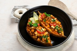 Stuffed sweet potato with spiced chickpea, dressing and herbs. Homemade vegan food concept. Copy space