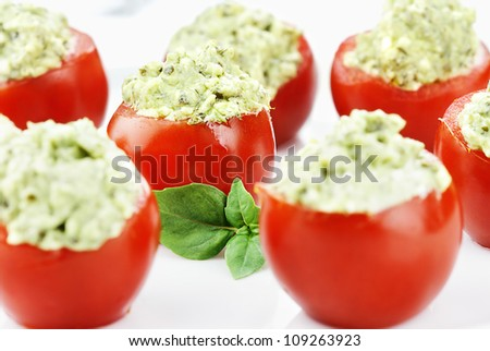 Stuffed Tomatoes filled with a pesto and avocado mixture. Extreme shallow depth of field with selective focus on center tomato.