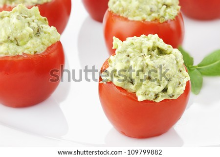 Stuffed Tomatoes filled with a pesto and avocado mixture. Extreme shallow depth of field with selective focus on tomato in foreground.