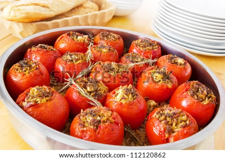 Stuffed tomatoes in a round casserole fresh out of the oven, filled with pasta, mince meat and feta cheese. Decorated with rosemary twigs, bread and dishes