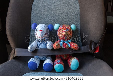 Stuffed toys buckled with safety belt in a car