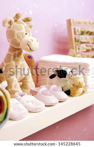 Stuffed toys shoes and nappies on shelf in baby\'s room