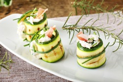 Stuffed zucchini rolled with cream cheese on complex background