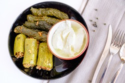 Stuffed zucchini with minced meat and rice. Stuffed leaves (yaprak sarma) presentation with yogurt, knife, fork and spoon on white background. Popular traditional food of Turkey and Middle East.