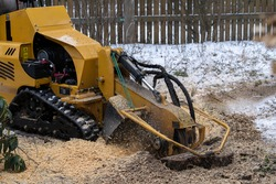 Stump grinding with a view from the right where the cutting disc is visible in close proximity. During the grinding process, the stump shavings fly through the air. The yellow stump grinder grinding