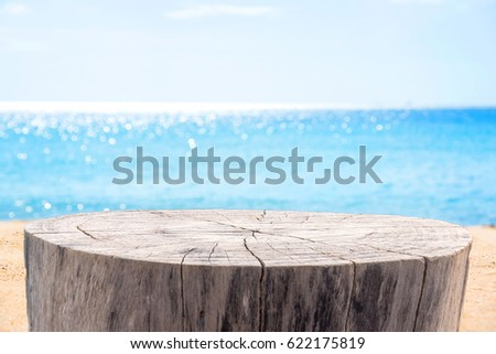 Stump table on sandy beach with blurred blue sea background.