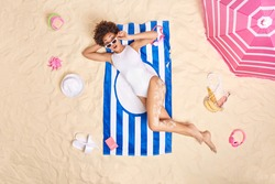 Stunned Afro American woman with curly hair wears white bikini sunglasses poses on striped towel has shocked expression poses at white sand with beach accessories around. Summer time vacation concept