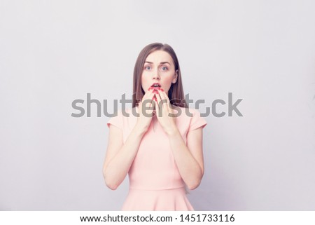 Stunned amazed woman girl closes her mouth in surprise, reacts to unexpected news, portrait, copy space