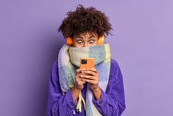 Stunned beautiful millennial girl with curly bushy hair stares at smartphone display scrolls news in internet wears wireless headphones velvet jacket scarf around neck isolated over purple background