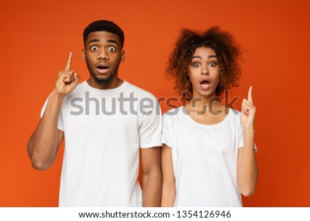 Stunned black man and woman pointing upward with opened mouths in amazement, orange background