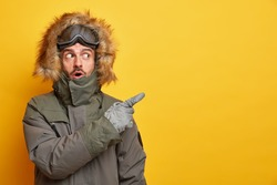 Stunned Caucasian man in winter clothes points away on blank space with surprised expression goes skiing during cold day wears jacket and gloves enjoys chilly weather isolated on yellow background
