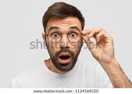Stunned emotive unshaven young guy stares with eyes popped out, keeps jaw dropped, sees or hears something bad or unpleasant, expresses great surprisement. People, negative emotions, feelings concept #1124568320