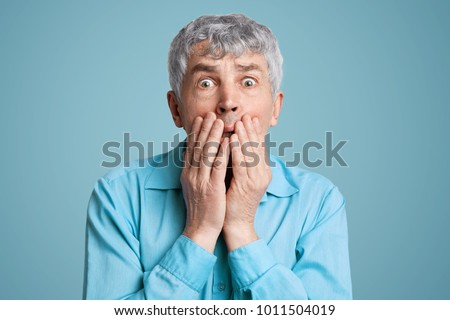 Stunned frightened elderly male model covers mouth with hands, being surprised and scared to hear shocking news, can`t believe in disaster, isolated over blue background. People and reaction #1011504019