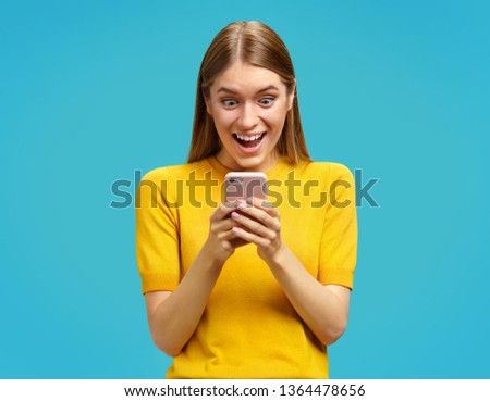Stunned girl having widely opened eyes and mouth, looks at the phone. Photo of girl in yellow sweater on blue background. Omg concept