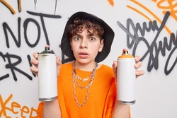 Stunned handsome hipster guy holds two aerosol spray bottles makes graffiti wall wears hat and orange t shirt damages street buildings. Abstract background. Urban lifestyleand vandalism concept