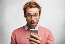 Stunned male executive recieves bad news on smart phone, looks with terrified expression at screen, reads sms message, expresses surprisment. People, human reaction, shock and technology concept