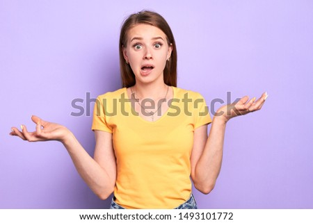Stunned young female has clueless and puzzled face expression, doesnt know what to do with problem situation, stands with wide opened eyes and mouth, shruggs shoulders, feels confused.