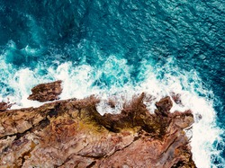 Stunning aerial top view of sea waves hitting rocks on the beach with foam