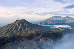 Stunning aerial view of a beautiful mountain range surrounded by clouds during sunrise. Ijen Volcano complex. The Ijen volcano complex is a group of composite volcanoes located in East Java, Indonesia