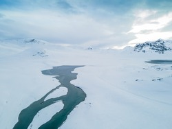 Stunning aerial view of a river flowing through a snow covered tundra and mountain range.