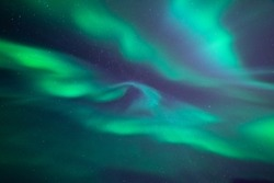 Stunning aurora borealis. Shape of fast moving lights of crown aurora. Looking directly up in the sky. Northern ligths, green purple and blue colors.