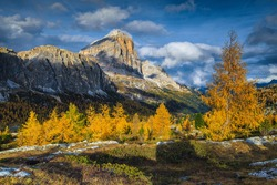 Stunning autumn alpine landscape with colorful redwood forest and beautiful yellow larches. Amazing clouds over the magical high mountains at sunset, Passo Falzarego, Dolomites, Italy, Europe