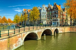 Stunning autumn landscape, Amsterdam canals and typical dutch houses in capital of Netherlands, Europe