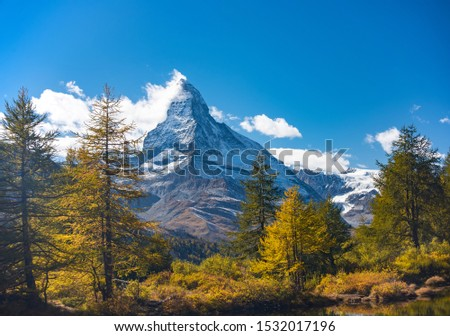 Stunning autumn scenery of famous alp peak Matterhorn capped by snow and yellowed larches on foreground. Swiss Alps, Valais, Switzerland #1532017196