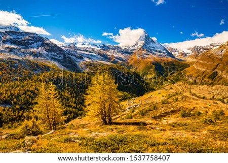 Stunning autumn scenery of famous alp peak Matterhorn capped by snow and yellowed larches on foreground. Swiss Alps, Valais, Switzerland #1537758407