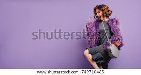 Stunning barefooted woman in trendy fur coat dancing and laughing on photoshoot. Indoor photo of lovely girl with short hairstyle fooling around on purple background.
