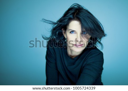 stunning beautiful and self confident middle aged woman with black hair smiling into camera portrait