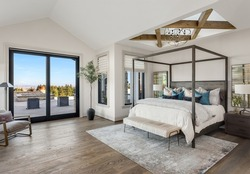 Stunning bedroom in new luxury home. Features sliding glass doors leading to patio, skylight overhead with wood beams and pendant light, hardwood floor, and elegant furnishings.