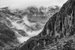 Stunning  black and white Winter landscape image of view from Side Pike towards Langdale pikes with low level clouds on mountain tops and moody mist