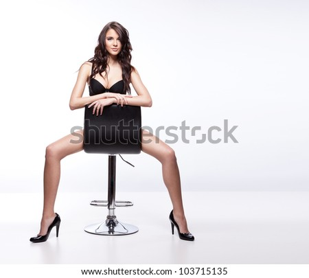 Stunning brunette sitting and posing on a chair