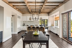 Stunning Dining room and Kitchen in New Luxury Home. Wood beams and elegant pendant lights accent the beautiful open floor plan, dining room, and kitchen.