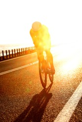 stunning early morning shot of a triathlete riding their bike bicylce on the open road during an ironman competition between cairns and port douglas australia. Road racing cycling. pro rider, cycling