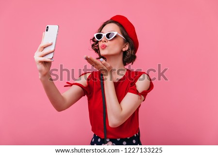 Stunning french woman sending air kiss while taking picture of herself. Indoor portrait of romantic curly lady in betet making selfie on pink background.