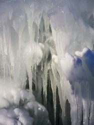 Stunning frozen icicles waterfall on a rocky mountain cliff on a winter day. The winter cascade is frozen in numerous white icicles. Waterfall falling past hundreds of icicles fantastic winter landsca