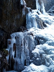 Stunning frozen waterfall icicles on rocky mountain cliff on winter day. A frozen waterfall with ice in a blue and white color in winter, A high altitude frozen falls near Leh in Ladakh, India.