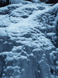 Stunning frozen waterfall icicles on rocky mountain cliff on winter day. Winter cascade frozen into numerous white icicles. Waterfall falling past hundreds of icicles Fantastic winter scenery,