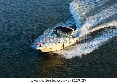Stunning image of a boat racing through the river in sunlight