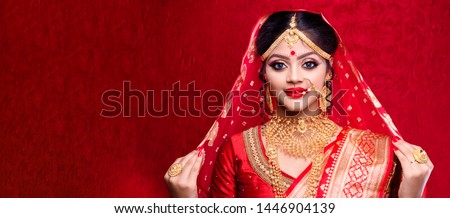 Stunning Indian bride dressed in Hindu red traditional wedding clothes sari embroidered with gold jewelry and a veil smiles tender with extra copy space.