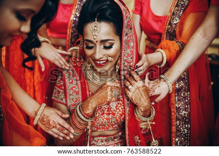 Stunning Indian bride dressed in Hindu traditional wedding clothes lehenga embroidered with gold and a veil gets ready with help of her bridesmaids
